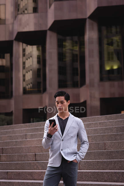 Front view of handsome Asian man using mobile phone while standing on stairs. He is looking surprised — Stock Photo