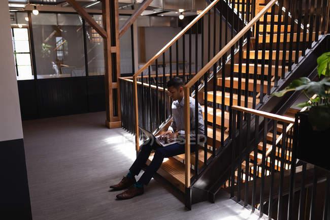 Вид збоку змішаної раси бізнесмен працює на ноутбуці, сидячи на сучасних сходах в сучасному офісі — стокове фото
