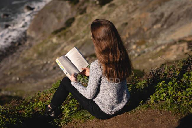 Заднього виду красивих жінок читанні книги, сидячи на схилі гори — стокове фото
