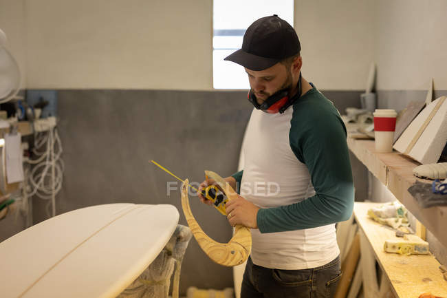 Side view of Caucasian man measuring surfboard with special ruler in a workshop — Stock Photo