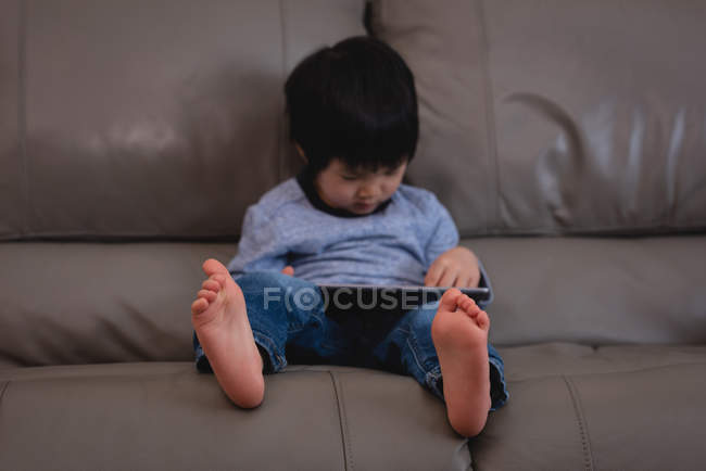 Frontansicht eines kleinen asiatischen Jungen mit digitalem Tablet, während er zu Hause auf dem Sofa sitzt — Stockfoto