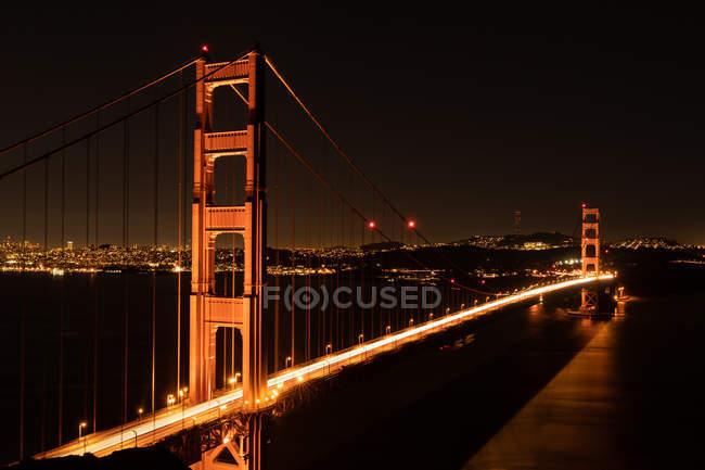 Vista frontal da ponte à noite com luzes e cidade no fundo — Fotografia de Stock