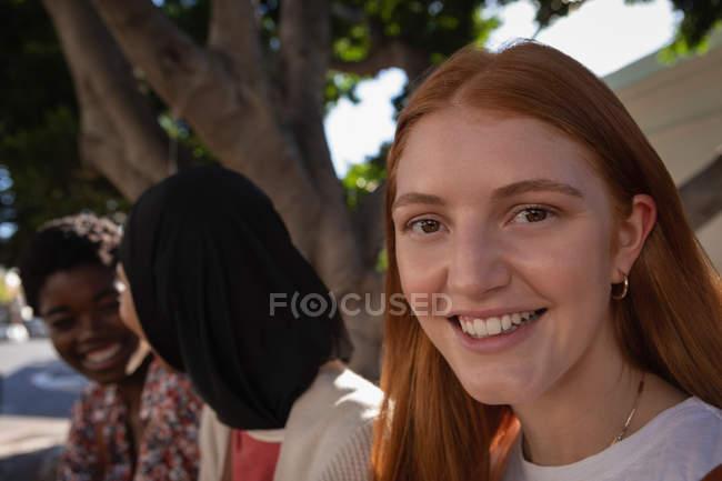 Portrait de belle jeune femme caucasienne assise sous l'arbre tandis que des amis parlent en arrière-plan — Photo de stock