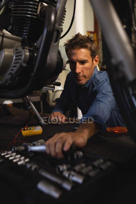 Front view of Caucasian male bike mechanic repairing bike in garage at workshop — стокове фото