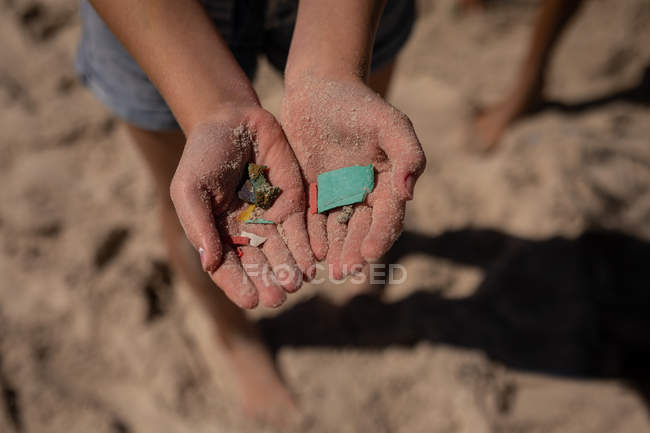 Close-up of volunteer holding waste in hand at beach on a sunny day — Photo de stock