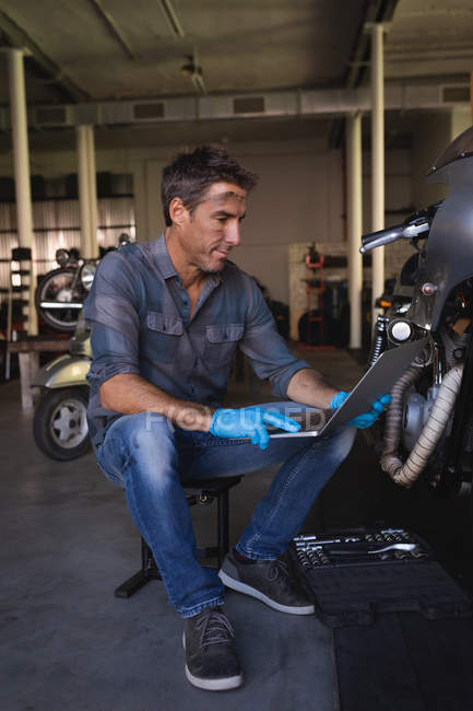 Side view of Caucasian bike mechanic wearing gloves while using laptop while working in garage — стокове фото
