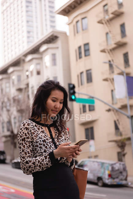Vue latérale de la femme asiatique utilisant un téléphone mobile tout en se tenant sur la rue — Photo de stock