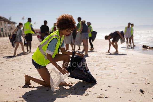 Seitenansicht der jungen gemischten Rasse weibliche Freiwillige Reinigung Strand an einem sonnigen Tag — Stockfoto
