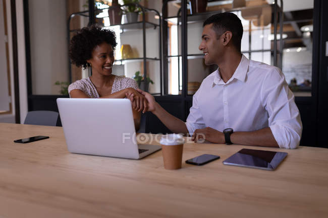 Vista frontal de personas de negocios de raza mixta que interactúan entre sí en la oficina moderna mientras se estrechan la mano con la pantalla digital en primer plano - foto de stock