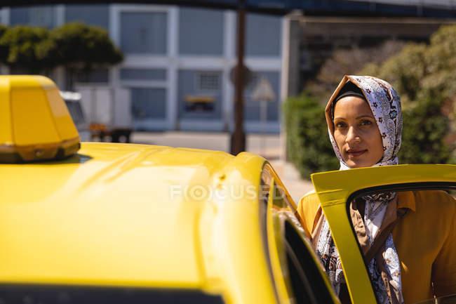 Vista frontal de la reflexiva mujer de raza mixta mirando a la cámara mientras se sube al taxi en la calle - foto de stock