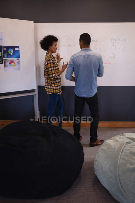 Rear view of young mixed-race business people interacting with each other on project over whiteboard standing in modern office — Photo de stock