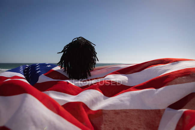 Rear view of young African American man holding american flag at beach on a sunny day — Foto stock