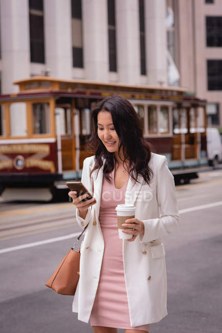 Front view of happy Asian woman smiling and using her mobile phone while having coffee at street — Stock Photo