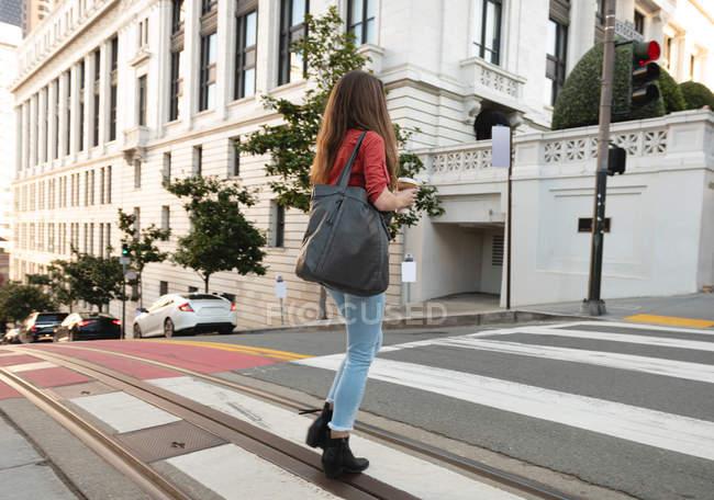 Vista laterale della donna in piedi sull'attraversamento zebra in strada — Foto stock