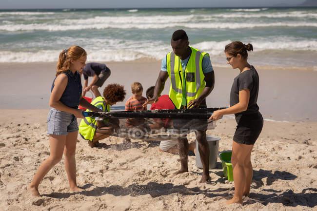 Seitenansicht einer Gruppe von mehrethnischen Freiwilligen, die den Strand mit spezialem Sieb reinigen, während die anderen Freiwilligen an einem sonnigen Tag in Hocke hinter ihnen sitzen — Stockfoto