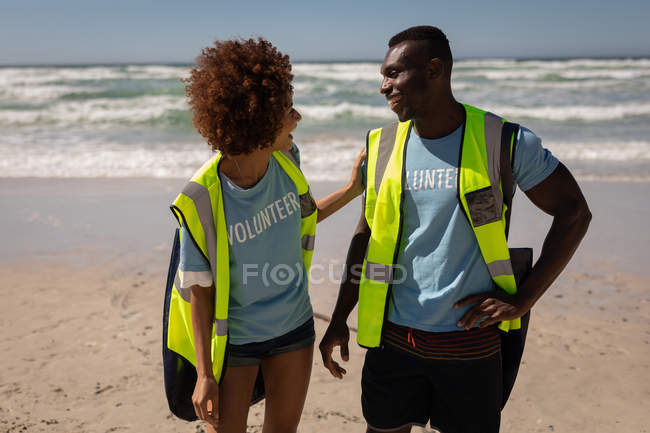 Front view of two happy multi ethnic volunteers interacting with each other on the beach — Stock Photo