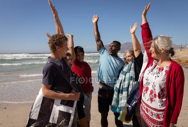 Front view of multi ethnic group of Volunteers forming hand stack on the beach — Stock Photo