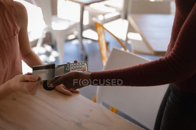Mid section of woman making payment through credit card in a cafe — Stock Photo