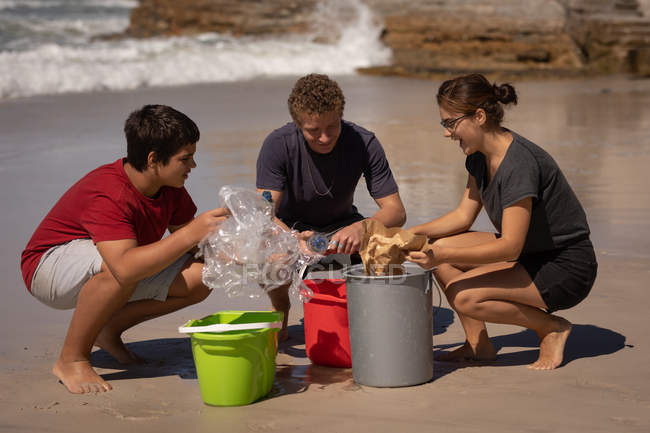 Front view of group of multi ethnic volunteers cleaning beach while sitting in squat position in front of buckets on a sunny day — Stock Photo
