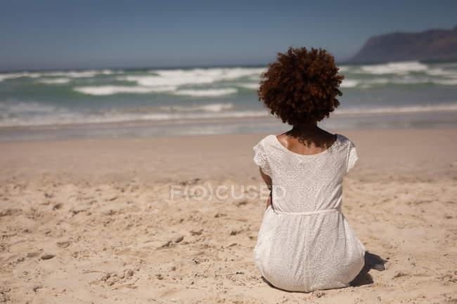 Заднього виду змішаної жінки гонка в біле плаття, сидячи на піску, відпочиваючи на пляжі на сонячному — стокове фото