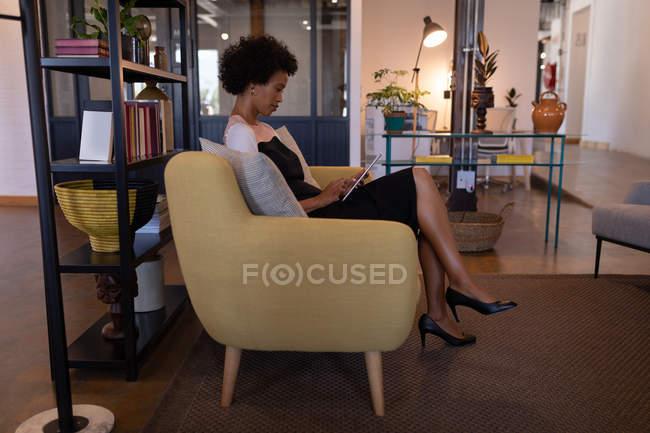 Vista laterale di bella donna d'affari mista che utilizza tablet digitale in ufficio moderno mentre è seduta su un sedile moderno contro gli arredi in background — Foto stock