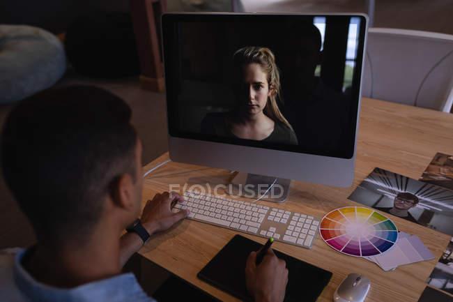 Vista posteriore del grafico maschile a gara mista che utilizza un tablet grafico per progettare un modello donna sullo schermo nell'ufficio moderno — Foto stock