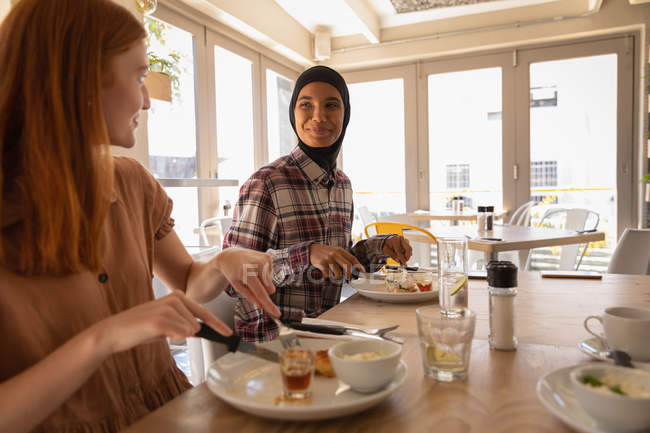 Side view of mixed race female friends interacting with each other while having breakfast in restaurant — Stock Photo