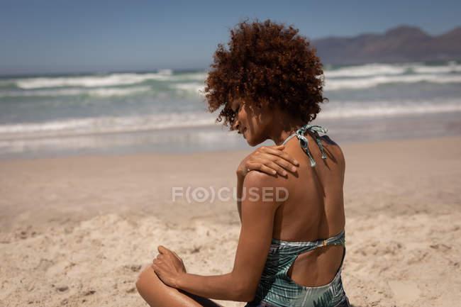 Visão traseira da mulher muito mista colocando protetor solar loção em seu ombro na praia em um ensolarado — Fotografia de Stock