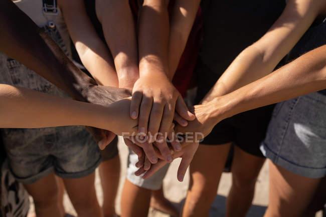 Seção meados de grupo de voluntários que formam a pilha das mãos na praia — Fotografia de Stock
