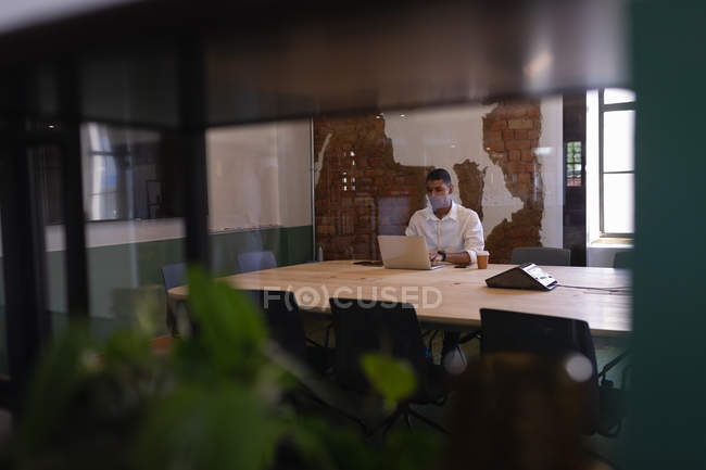 Front view of young mixed-race businessman working over laptop at desk in modern office — Stock Photo