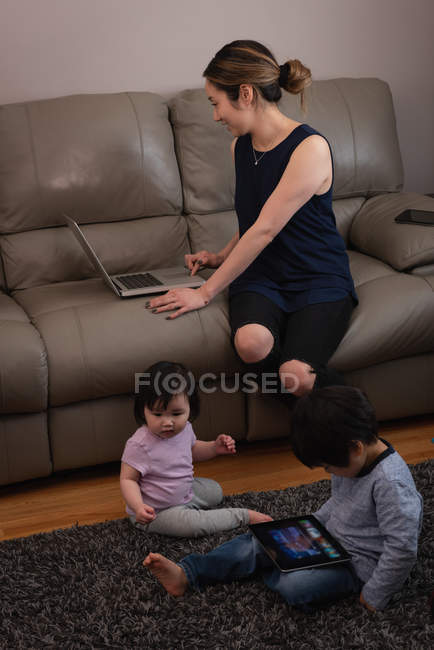 Front view of an Asian mother using laptop and sitting on the sofa while kids playing on rug with digital tablet at home — Stock Photo