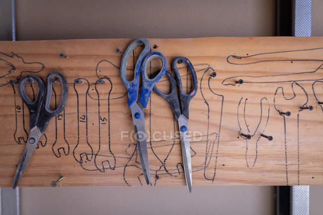 Tre forbici che pendono su unghia a workshop — Foto stock