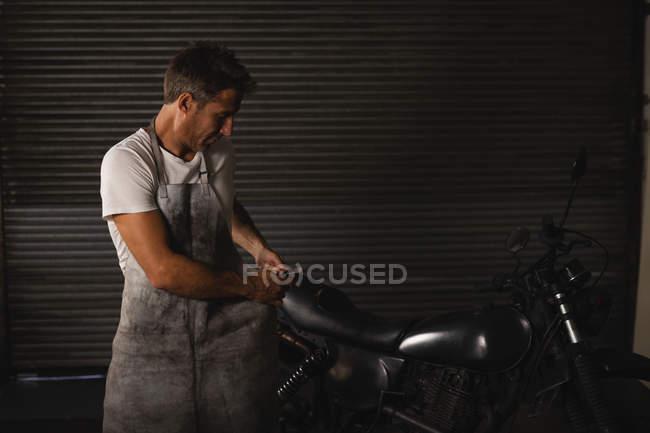 Front view of Caucasian male bike mechanic fixing bike and wearing apron in garage — Stock Photo