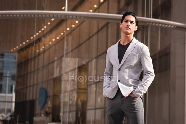 Thoughtful handsome man standing near building — Stock Photo