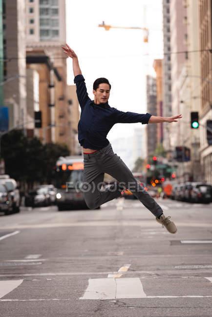 Vista frontale del bel giovane asiatico che salta e balla per strada — Foto stock