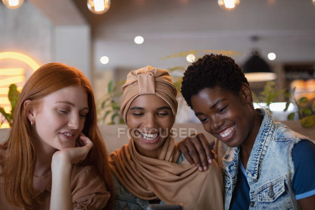 Front view of happy mixed race female friends using mobile phone while sitting in the restaurant — Stock Photo
