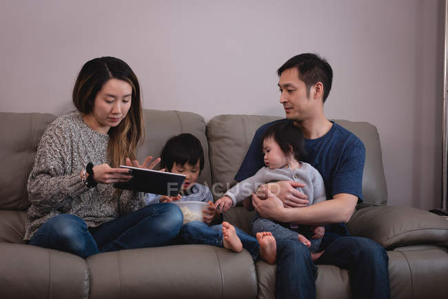 Front view of  Asian family enjoying together while sitting on sofa with tablet and pop-corn at home — Stock Photo