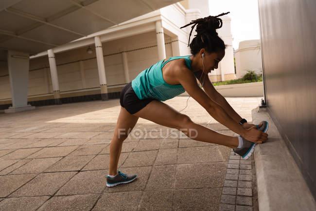 Вид сбоку на молодую женщину смешанной расы, слушающую музыку в наушниках во время тренировки в городе — стоковое фото