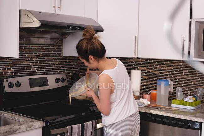 Vue arrière de la femme asiatique versant un mélange de crêpes dans une poêle à frire dans la cuisine à la maison — Photo de stock