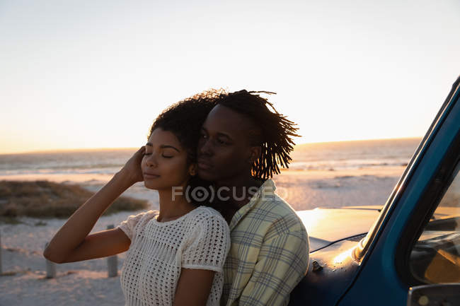 Side view of romantic African American couple leaning at car on beach at sunset — Photo de stock