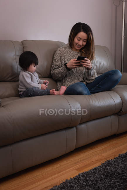 Front view of a happy Asian mother and daughter using mobile phone while sitting on sofa at home — Stock Photo