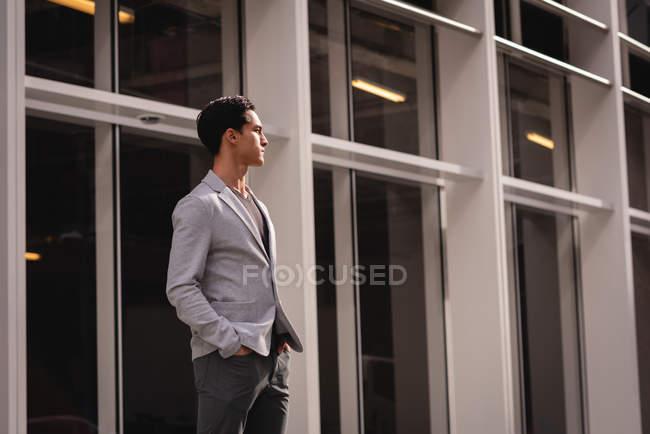 Vorderansicht eines nachdenklichen asiatischen Mannes, der in der Nähe eines Gebäudes steht — Stockfoto