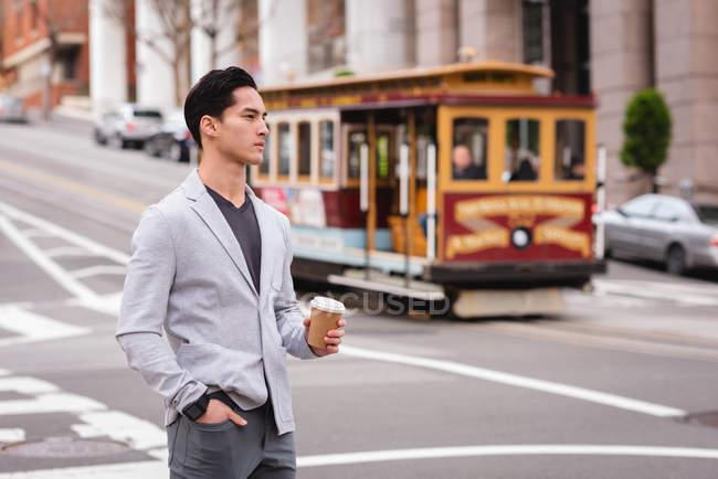 Vorderansicht eines hübschen asiatischen Mannes, der auf der Straße steht, während er Kaffee trinkt — Stockfoto