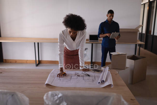 Front view of Mixed-race businesswoman looking at blueprint while mixed-race businessman using digital tablet at office in background — Stock Photo