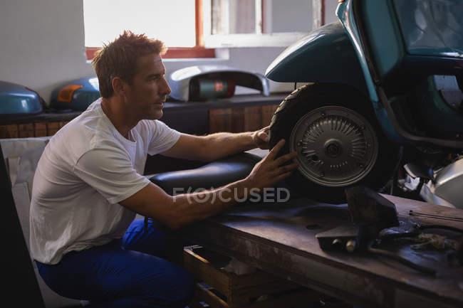 Side view of Caucasian male bike mechanic repairing motorbike tire in garage — стокове фото