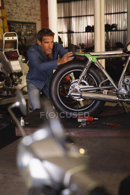 Front view of Caucasian male bike mechanic fixing new seat in motorbike at garage — Stock Photo