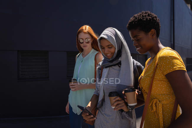 Side view of young mixed race female friends interacting with each other while walking in the city street — Stock Photo