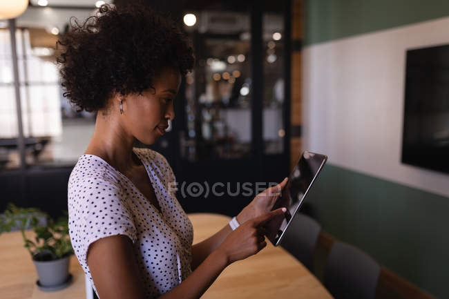 Side view of beautiful Mixed-race businesswoman using digital tablet standing in modern office — Stock Photo