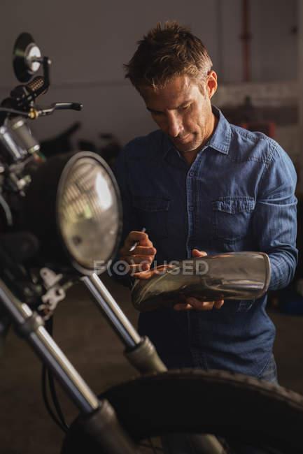 Front view of Caucasian male bike mechanic holding mudguard in garage — стокове фото