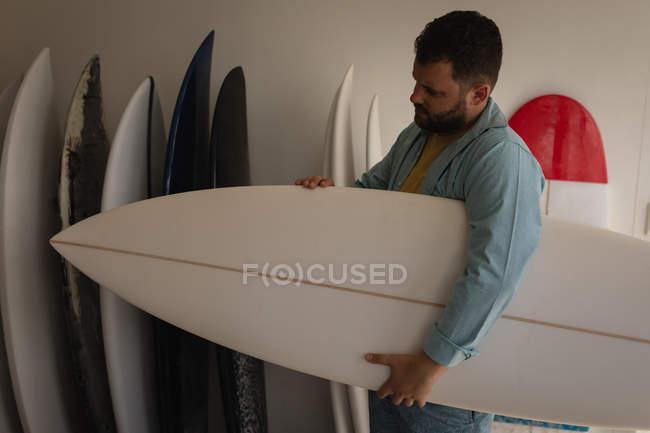 Vista laterale dell'uomo caucasico che tiene una nuova tavola da surf mentre guarda la sua creazione in un laboratorio — Foto stock